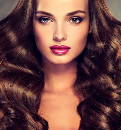 long red hair woman: Nice young girl model with dense, curly hair. Bright fashionable make up and hairstyles.
