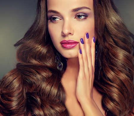 Nice young girl model with dense, curly hair. Bright fashionable make up and hairstyles.