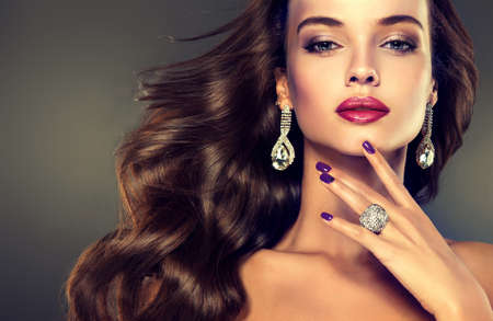 Mooi jong meisje model met dichte, krullend haar. Heldere trendy make-up en kapsels. Stockfoto