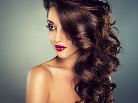 Bright fashionable makeup. Nice young girl model with dense, curly hair.