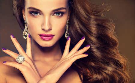 aretes: Bella modelo morena con el pelo largo rizado. estilo de la moda de lujo, manicura uñas, cosméticos, maquillaje Foto de archivo