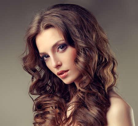 Beau modèle brune aux cheveux longs bouclés. Gros plan de portrait de jeune fille.