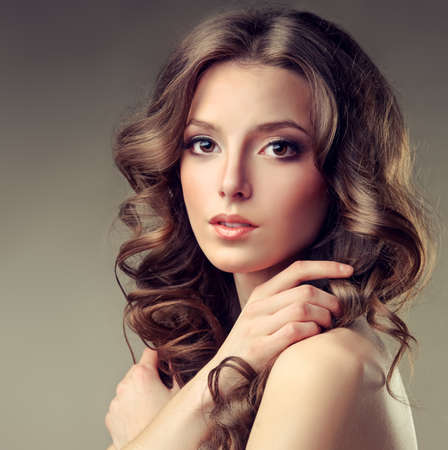 Beautiful model brunette with long curled hair.Close-up portrait of young girl.
