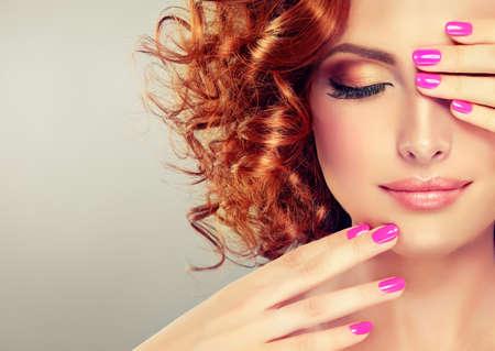 Bastante chica de pelo rojo con rizos, la moda de maquillaje y manicura rosa.
