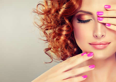 Pretty red haired girl with curls , fashionable makeup and pink manicure.