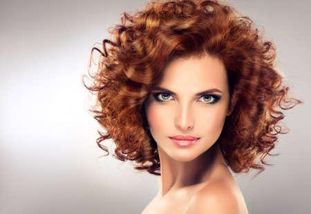 Jolie rouge fille aux cheveux avec des boucles, le maquillage à la mode. Regardez droit devant la caméra. Banque d'images - 52034935