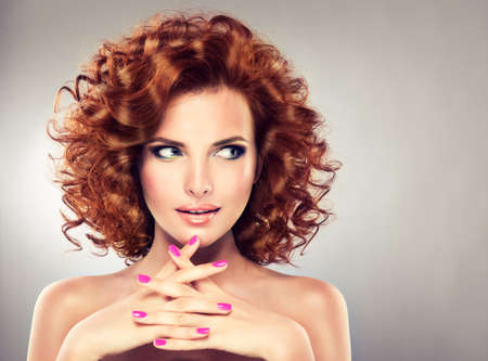 Pretty red haired girl with curls , fashionable makeup and pink manicure. Tricky glance.