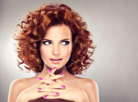 Pretty roodharige meisje met krullen, trendy make-up en roze manicure. Tricky oogopslag.