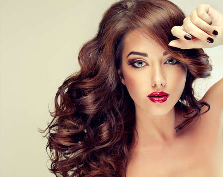 hair model: Model with dense, curly hair. Luxury fashion style, manicure, cosmetics and make-up. Stock Photo