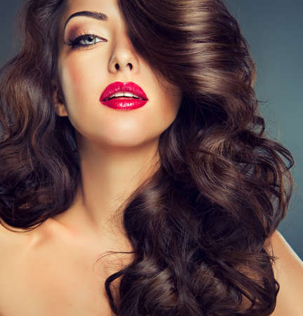 long curly hair: Model with dense, curly hair. Luxury fashion style, manicure, cosmetics and make-up. Stock Photo
