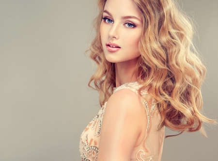 evening gown: Young beautiful woman, dressed in evening gown. Loose,wavy hair and bright make up.