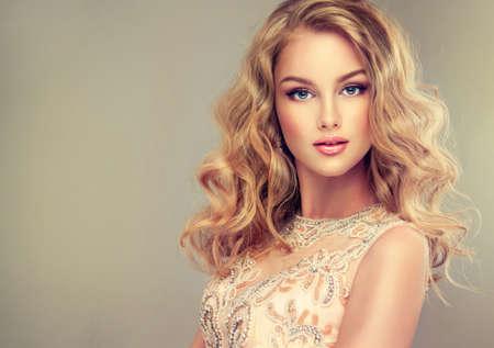 cabello rubio: Joven y bella mujer, vestida en traje de noche. Suelta, el pelo ondulado y brillante maquillaje.
