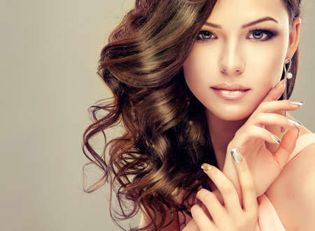 Portrait of young model with wavy, dense hair, silver lipstick and french-style manicure. Standard-Bild