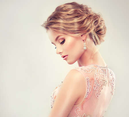 Example of wedding hairstyle. Beautiful girl light brown hair with an elegant hairstyle.