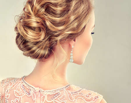 Example of wedding hairstyle. Beautiful girl light brown hair with an elegant hairstyle.View from back side.