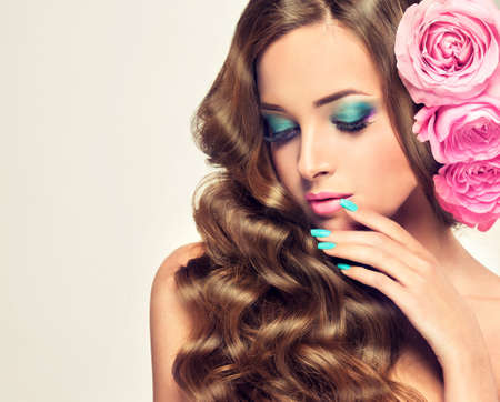 Beautiful model brunette with long and lush curled hair. Pink roses in the hair.