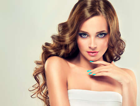 カールした髪の長く、豊かな美しいモデル ブルネット。高級ファッションのスタイル、爪のマニキュア、化粧品とメイクアップ。