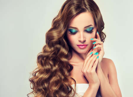 Beautiful model brunette with long and lush curled hair. Luxury fashion style, nails manicure, cosmetics and make-up.