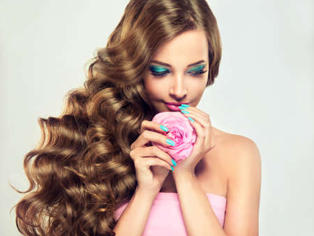Beautiful model brunette with long and lush curled hair , pale-pink rose flower in the hands.