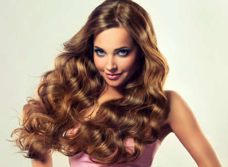 Beautiful model brunette with long and lush curled hair. Luxury fashion style.