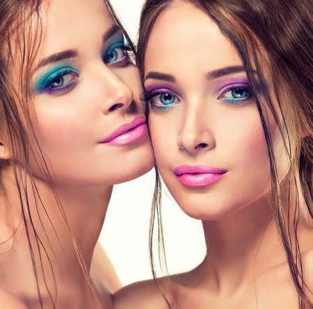Primer plano retrato doble de jóvenes hermosas modelos de la moda, con el pelo enorme, violeta perfecto maquillaje y manicura rosa.
