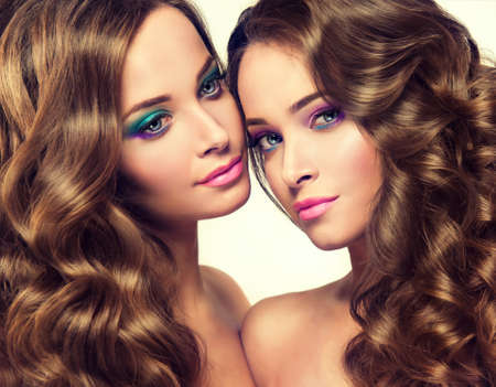 Close-up double  portrait of young gorgeous fashion models, with lush hair, perfect violet make-up and pink manicure.
