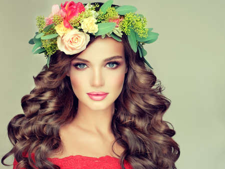 perming: Beautiful woman model brunette with long curly hair floral wreath on the head . Spring girl.