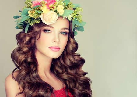 primavera: Hermosa modelo de mujer morena con una larga guirnalda floral pelo rizado en la cabeza. Niña de primavera.