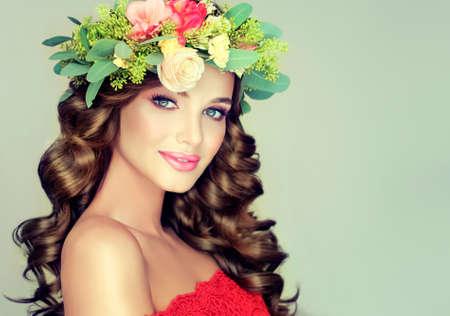 belle brune: Belle brune modèle femme avec de longs cheveux bouclés couronne de fleurs sur la tête. Spring girl. Banque d'images