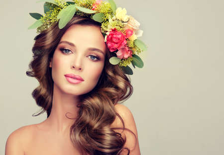 Beautiful woman model brunette with long curly hair floral wreath on the head . Spring Lady. Standard-Bild