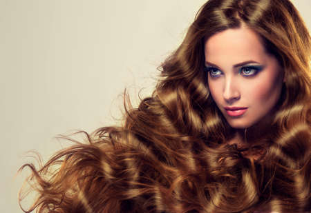 Beautiful model brunette with long and lush curled hair. Luxury fashion style, cosmetics and make-up. Archivio Fotografico