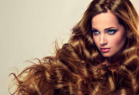 Piękny model brunetka z długimi włosami i bujnym zwinięty. Luksusowy styl mody, kosmetyków i makijażu. Zdjęcie Seryjne