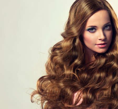 Bella modelo morena con el pelo largo y rizado exuberante. estilo de lujo de la moda, los cosméticos y el maquillaje.