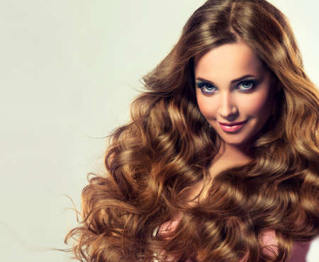 Beautiful model brunette with long and lush curled hair. Luxury fashion style, cosmetics and make-up. Banco de Imagens