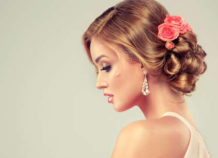 Bella donna con il trucco colorato e acconciatura matrimonio di moda. Rosa fiori nei capelli.