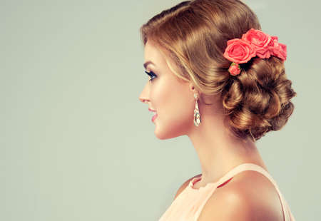 wedding hairstyle: Beautiful woman with colourful makeup and fashion wedding hairstyle. Rose flowers in the hair. Stock Photo