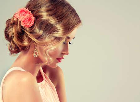 Beau modèle avec coiffure élégante. Belle femme avec le maquillage coloré et coiffure de mariage de la mode. Rose des fleurs dans les cheveux.