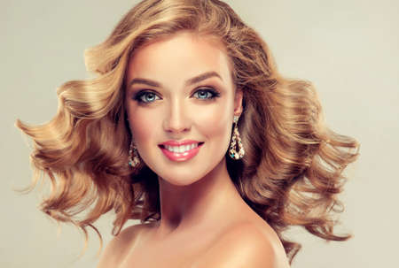 Young and beautiful smiling lady with dense, curled loose hair. Pale-blue eyes, gorgeous make-up, happy face.