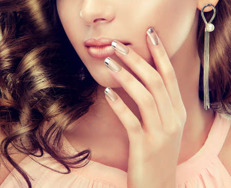Close-up image silver colored lips and french-style manicure.