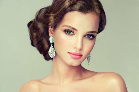 Giovane, bellissima modella mettere su in un delicato make up, e vestito con un abito rosso. Misty, look romantico. Matrimonio e la sera stile.