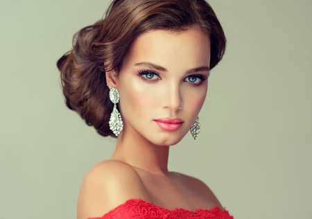 Young, gorgeous model putting on in a delicate make up, and dressed in a red gown. Misty, romantic look. Wedding and evening style.