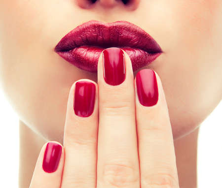 Beautiful model shows red manicure on nails. Red lips .Luxury fashion style, manicure nail , cosmetics and makeup