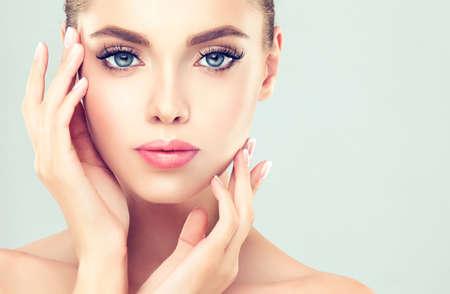 caras: Primer plano retrato de mujer joven con la piel limpia y fresca. El maquillaje y la manicura.