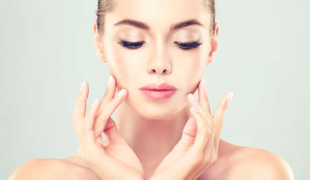 Close-up portrait of young woman with clean fresh skin. Make-up and manicure. Foto de archivo