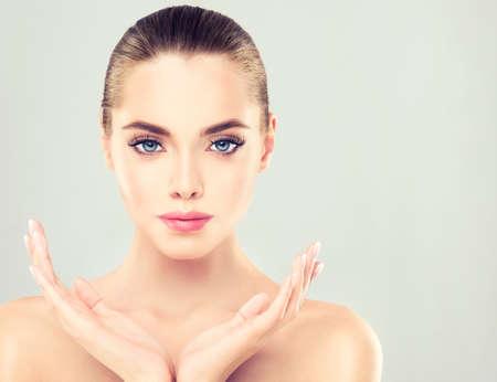 Close-up portrait de jeune femme à la peau douce et propre. Maquillage et manucure. Banque d'images - 58233019