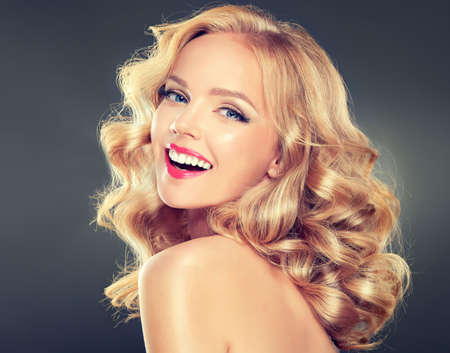 blonde haired: Young wide smiling blonde haired girl-model. Loose, dense,  blond hair, red make up and healthy teeth.