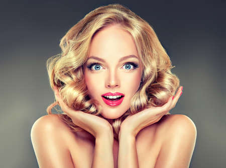 woman surprise: Young wide smiling blonde haired girl-model touching her dense blond hair. Surprised look.