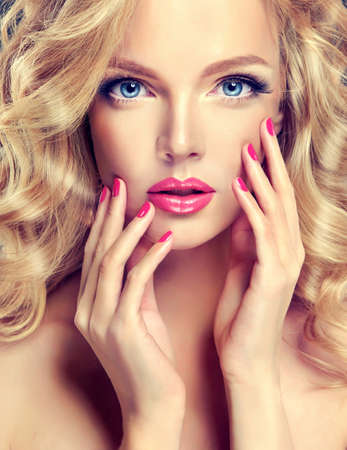 red nail: Close-up portrait of young gorgeous fashion model, with lush hair, perfect make-up and pink manicure. Stock Photo