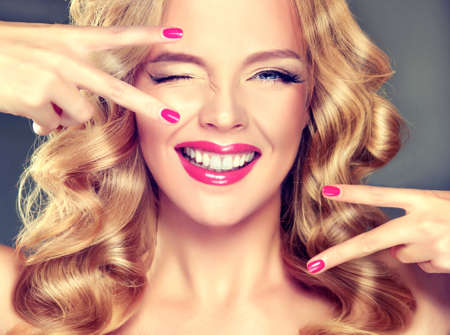 Young wide smiling blonde haired girl-model. Loose, dense,  blond hair, red make up and healthy teeth.