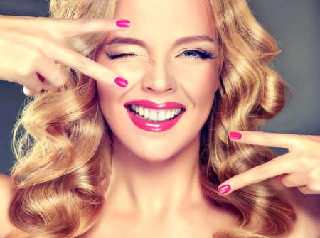 Jonge breed glimlachende blonde haired girl-model. Losse, dichte, blond haar, rode make-up en gezonde tanden. Stockfoto